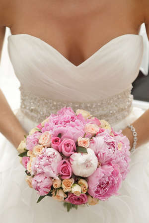 upper half: Beautiful wedding bouquet of pink and beige roses, paeonies in hands of the bride