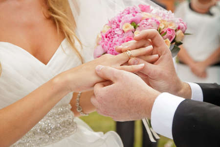 groom putting ring on brides finger, wedding