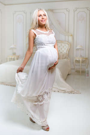 beautiful tender delicate pregnant blond woman in white dress touching her belly in white antique bedroom photo