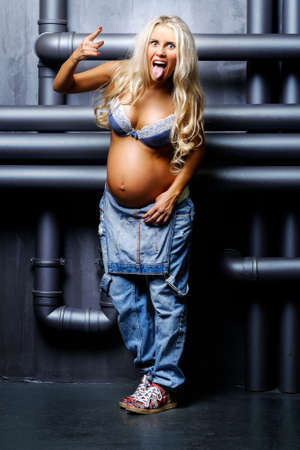 beautiful pregnant blond woman with naked belly showing her tongue and making a rock and roll gesture photo