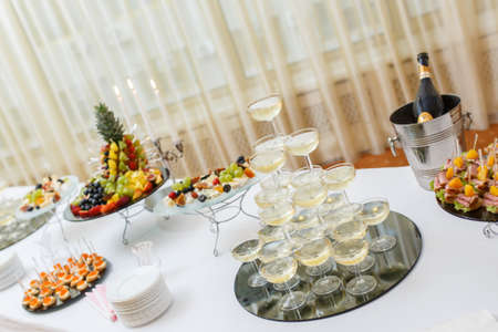 Table with cold snacks and tableware on luxury stand-up party, Champagne Pyramid photo