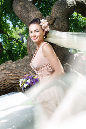 beautiful happy bride in beige dress smiling standing among green trees photo