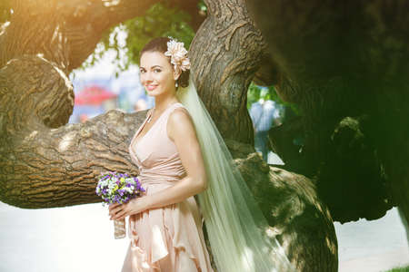beautiful happy bride in beige dress smiling standing among green trees in sunlight photo