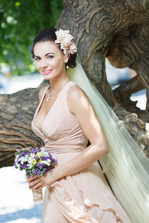 beautiful happy bride in beige dress with plunging neckline smiling standing among green trees photo