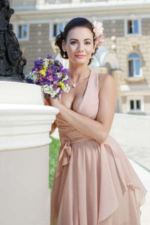 beautiful happy bride in beige dress with plunging neckline smiling standing near city building photo