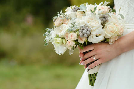 beautiful tender wedding bouquet of cream roses and eustoma flowers in hands of the bride
