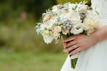 vackert anbud bröllop bukett grädde rosor och Eustoma blommor i händerna på bruden