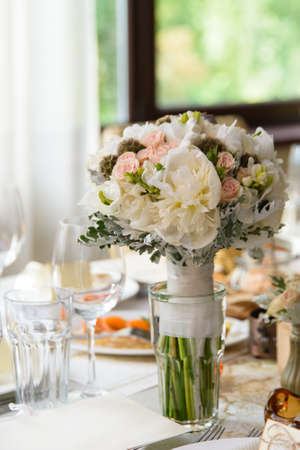 platycerium: Beautiful pastel wedding bouquet of roses, peony and freesia flowers on the table