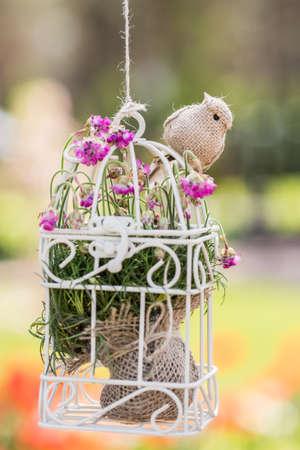 white birdcage with toy bird in vintage style, wedding decoration