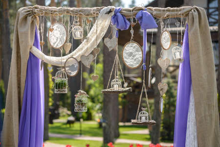 lilac handmade wedding arch decorated with dreamcatcher, Birdcage and heart in vintage style, photo zone
