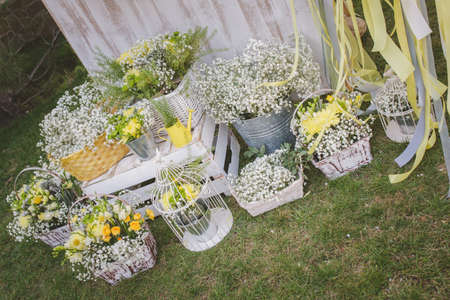 yellow wedding photo zone decorated with flowers, birdcage, bucket, basket, watering can in vintage style