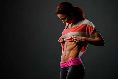 Foto van sportief meisje in studio kijken naar haar borst en blij met haar resultaten