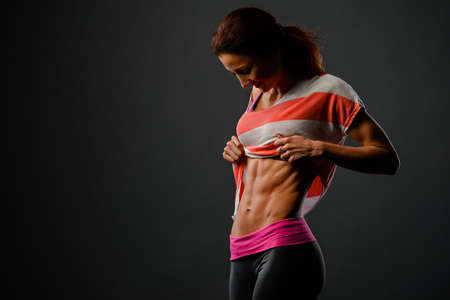 Photo of sporty girl in studio looking at her chest and happy with her results Stock Photo