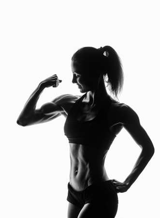 lady silhouette: silhouette of Young fitness lady posing with her biceps isolated on white