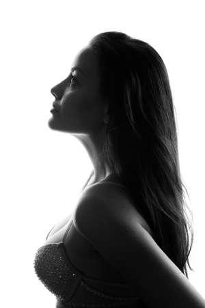 Silhouet van aantrekkelijke jonge vrouw geïsoleerd op wit in studio Stockfoto