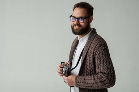 a creator: Portrait of positive hipster photographer with camera isolated in studio