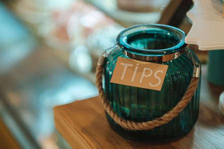De inscriptietips op een glazen antieke pot