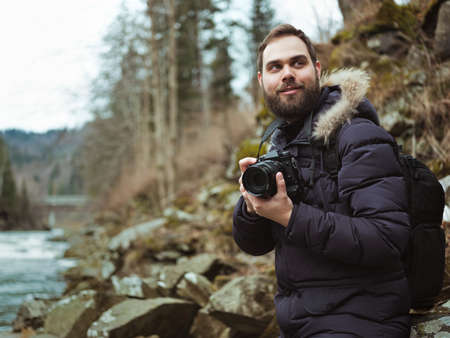 Man traveler photographer with camera photographing wildlife