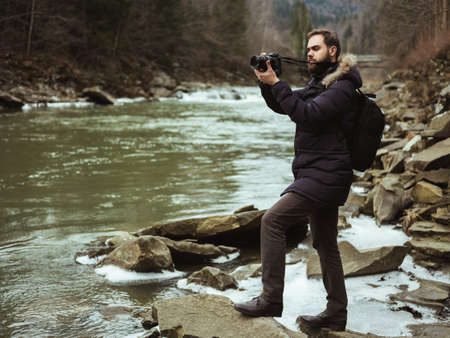 Man traveler photographer with camera photographing the river