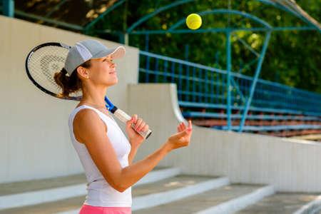 young sportive woman throwing a tennis ball Stockfoto