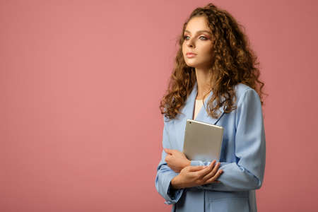 Closeup studio portrait of confident businesswoman with long curly hair holding electronic tablet and looking away from camera isolated on pink background and copy space on the left..