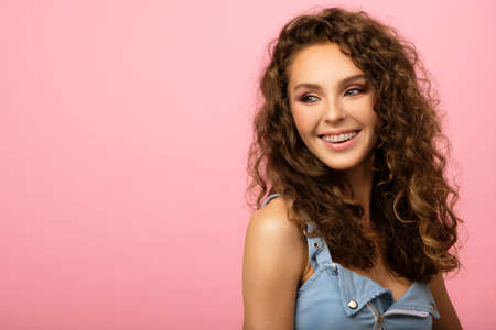 Closeup portrait of beautiful girl with long curly hair and dental braces on her pretty smile with white teeth isolated on pink background. Model is looking away from camera with copy space on left