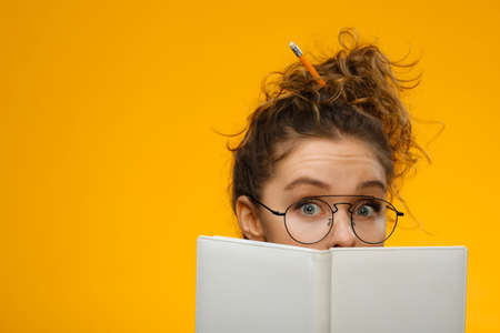 Closeup shot of attractive and charismatic teenage girl with curly hair wearing glasses. Model hiding behind white notebook with positive emotion