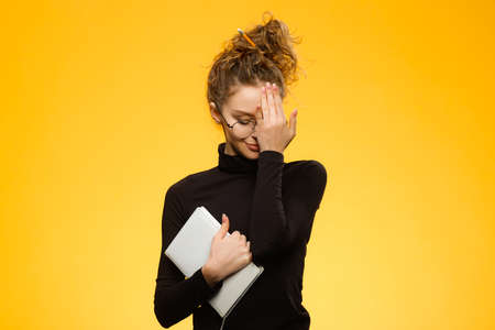 Closeup shot of attractive caucasian teenager wearing glasses and dental braces. Model is shy of camera and holding notebook in hands isolated on yellow background Foto de archivo