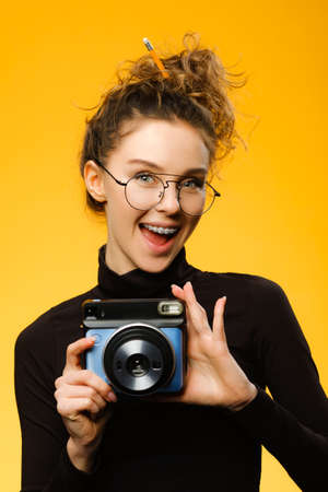 Closeup shot of cute female photographer with curly hair wearing glasses and dental braces. Model holding photo camera near her eye isolated on colorful yellow background