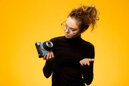 Pretty female photographer with curly hair and glasses trying to operate her instant camera isolated on yellow background