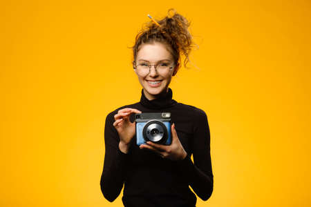 Closeup shot of cute female photographer with curly hair wearing glasses and dental braces.