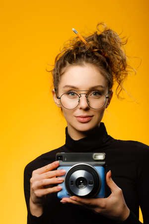 Closeup shot of cute female photographer with curly hair wearing glasses. Model looking at camera isolated on colorful yellow background