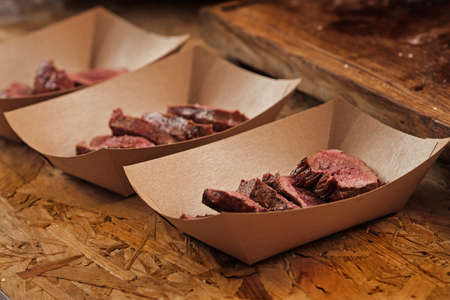 Closeup shot of delicious beef slices in craft paper container on street food festival Stock fotó