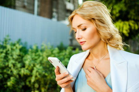 Closeup outdoor portrait of pretty businesswoman with a smartphone. Model has blond hair and wearing beautiful white suit.