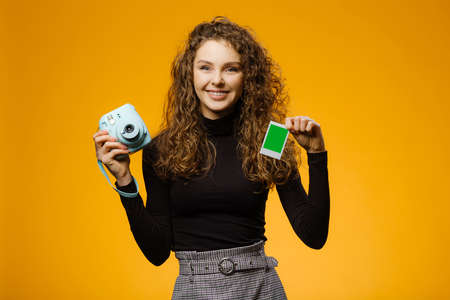 Beautiful girl with instant film camera isolated on yellow background. Model is holding blank frame with mockup space on a picture