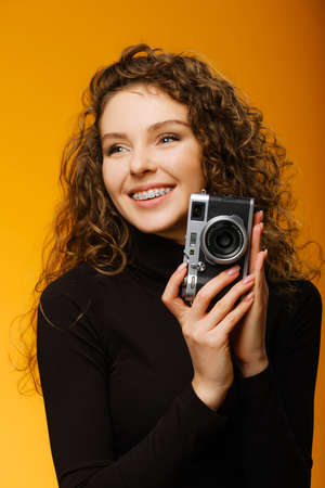 Happy girl with dental braces and white teeth isolated on yellow background. Concept of orthodontic treatment and healthy smile. Model posing with photo camera
