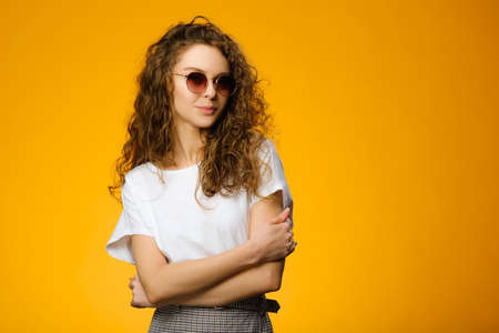 Pretty teenager wearing sunglasses and white shirt and looking at camera. Model isolated on colorful yellow background with copy space
