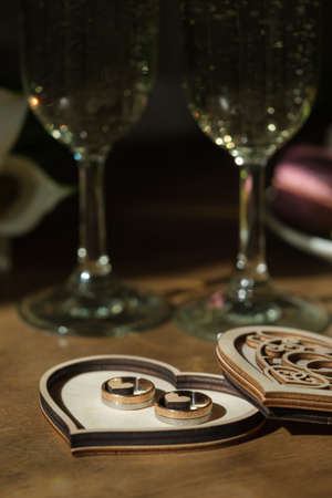 Golden wedding rings in a wooden box carved in a shape of heart with champagne glass on a background. Wedding celebration concept