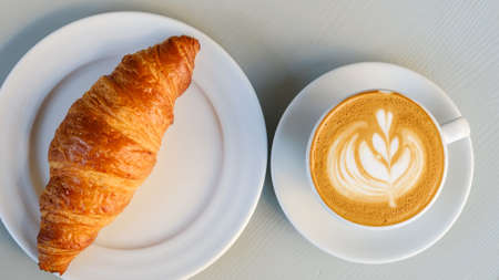 Top view on plates with croissant and latte with latte art on white table