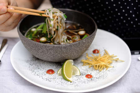 Traditional vietnamese pho bo soup with vegetables and beef in black bowl with male hands holding chopsticks Standard-Bild