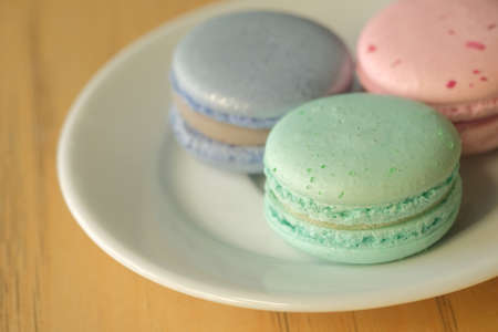 Top view on french macarons in pastel colors in white plate on wooden table