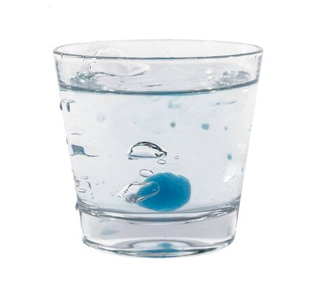 Blue ice cubes splashing into glass of water.