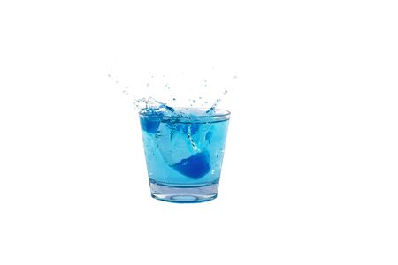 Blue ice cubes splashing into glass of water Stock Photo