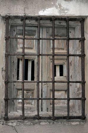 rejas de hierro: Ventana vieja abandonada con barras de hierro oxidadas. Foto de archivo