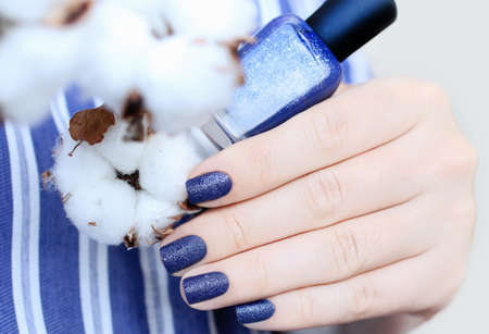 Sand textured manicure.Woman shows her nails,holding cotton in the hand.Cosmetics concept.