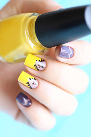 Bright yellow and purple woman manicure with nil art.Black ethnic ornament.