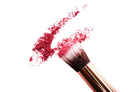 Crushed eyeshadow with make up brush.Isolated on white.Cosmetics concept.Top view.