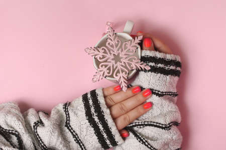Festive manicure with pink snowflake.Womans hands with beatiful manicure, in sweater. Christmas concept.