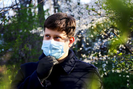 Man in blue medical maskand black gloves outdoor.Protecting health from various viruses and diseases.Quarantine and disease prevention concept.Family protection. 版權商用圖片