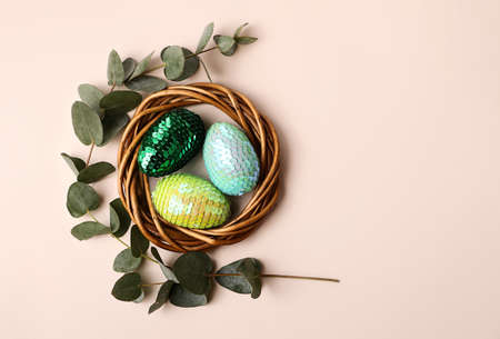 Colorful glossy easter eggs in the rattan nest.Natural eucalyptus branch on the back.Copy space for text or design. 版權商用圖片 - 148098555